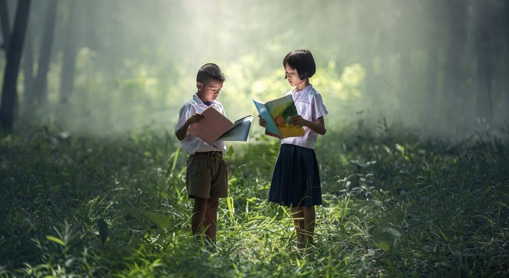 2 children reading books in the forest